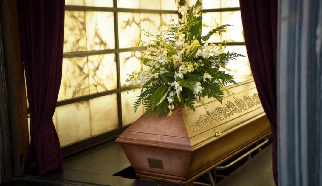 Sarg mit Blumenschmuck bei einer Beerdigung | Bildquelle: ©tomaspic - Fotolia.com