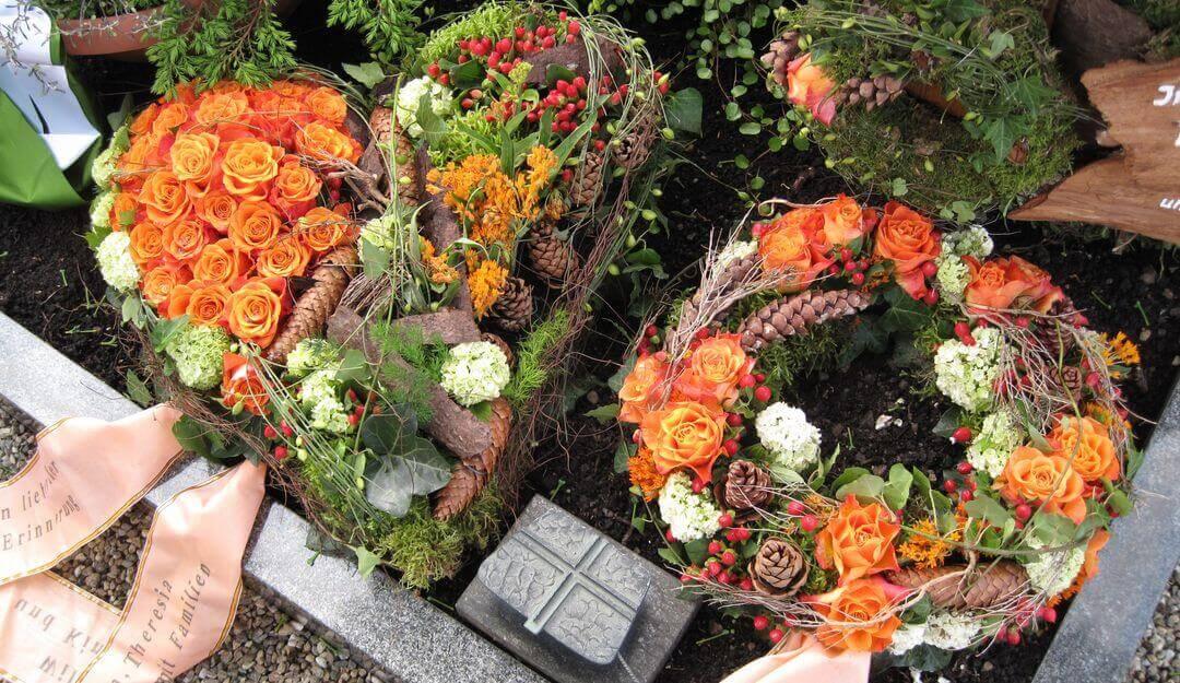 Grabgestecke zieren das Einzelgrab im Herbst und Winter. © Stilvolle-Grabsteine.de