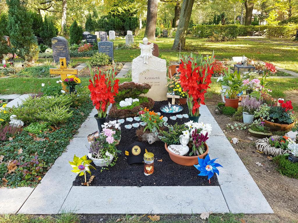 Schöne Gestaltungselemente für den Sommer sind Blumenschalen, kleine verzierte Steine und Grabfiguren.| Bildquelle: © Stilvolle Grabsteine