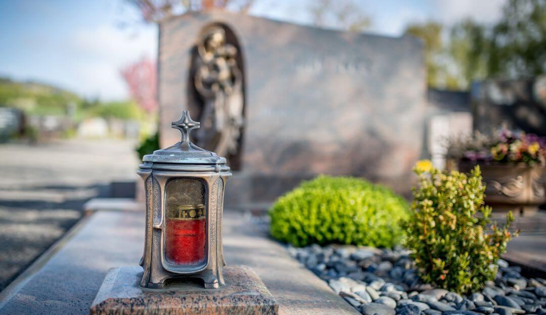 Kerzen oder Laternen werden an einem Grab niedergelegt, um sein Mitgefühl auszudrücken und die Wertschätzung gegenüber dem Verstorbenen auszudrücken. | Bildquelle: © mh90photo - Fotolia