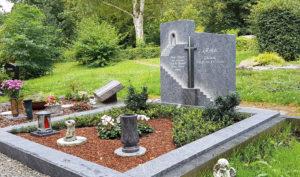 Doppelgrabstein mit Kreuz und pflegeleichter Grabgestaltung mit Rindenmulch.