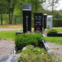 Einzelgrab mit sommerlicher Bepflanzung Grabeinfassung Grabstein schwarzer Granit poliert Grabstelen zweiteilig immergrüne Grab Bepflanzung