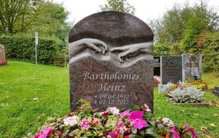 Urnengrab mit Grabbepflanzung / Blumen im Sommer - Einfassung & Urnengrabstein in Granit Paradiso (Motiv Michelangelo Berührende Hände) - Friedhof Hammerstedt