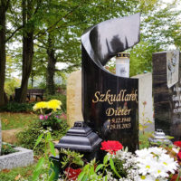 Moderner Urnengrabstein Granit mit Grabschmuck und Grabbepflanzung