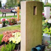 Urnengrab mit hellem Kalkstein Grabstein und Bepflanzung im Sommer und Herbst