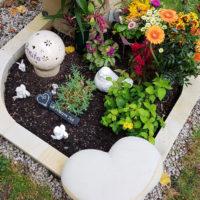 Urnengrab gestalten mit Grabschmuck & Grabdeko Blöumen Einfassung Herz Idee Beispiel