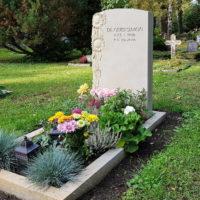 Sandstein Grabgestaltung mit Grabstein und Einfassung Grabdeko mit Ziergras Grablicht Blumen Sonnenblume Ornament Dresden Trinitatisfriedhof
