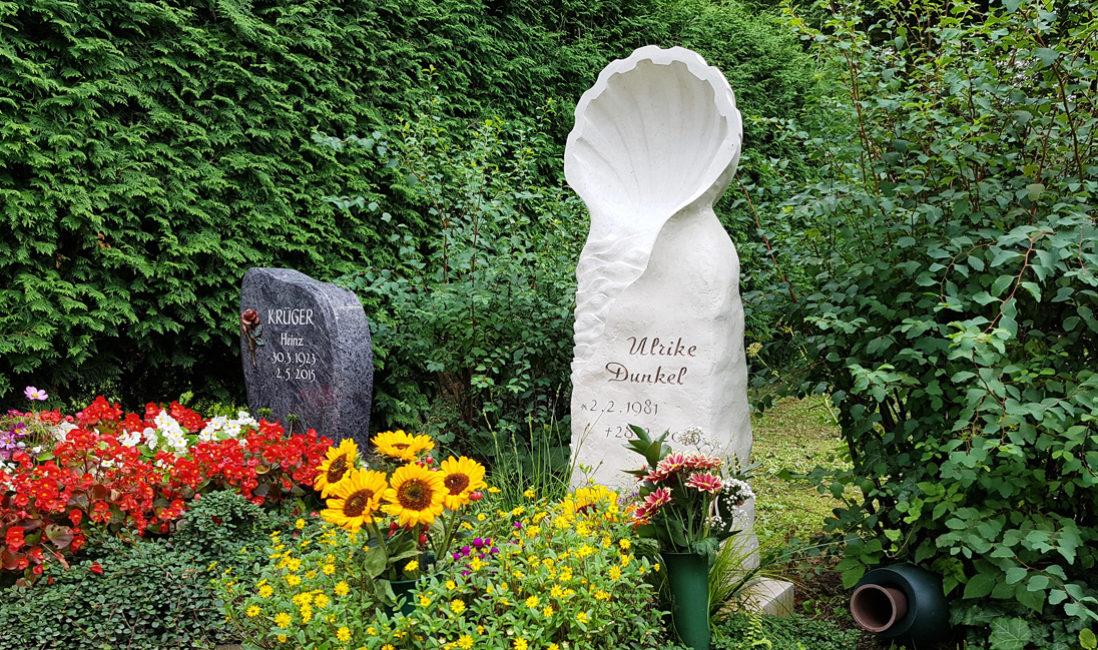 Grabstein als Stele Urnengrab Symbol Muschel Kalkstein gelbe Sommerblumen Grabpflege Sonnenblumen