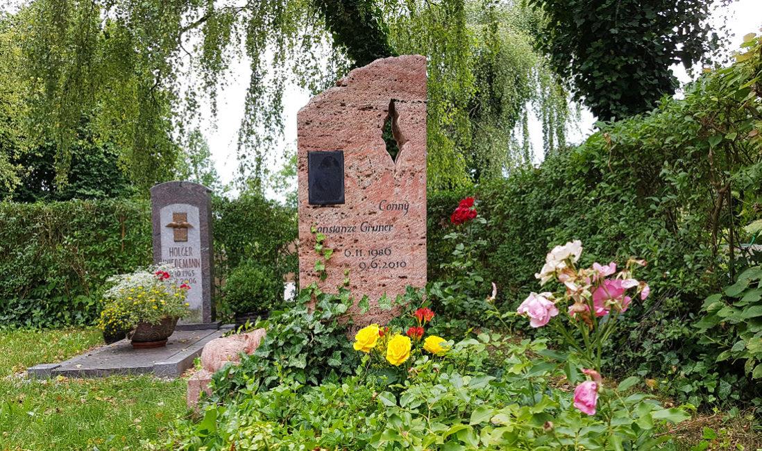Grabstein für ein Einzelgrabroter Travertin naturbelassen Öffnung  Portrait Lasergravur junger Mensch Grabbepflanzung mit Rosen und Efeu Friedhof Neustadt Orla