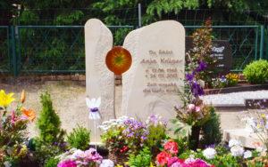 Frühlingshafte Grabgestaltung mit außergewöhnlichem Grabstein. © Stilvolle-Grabsteine.de