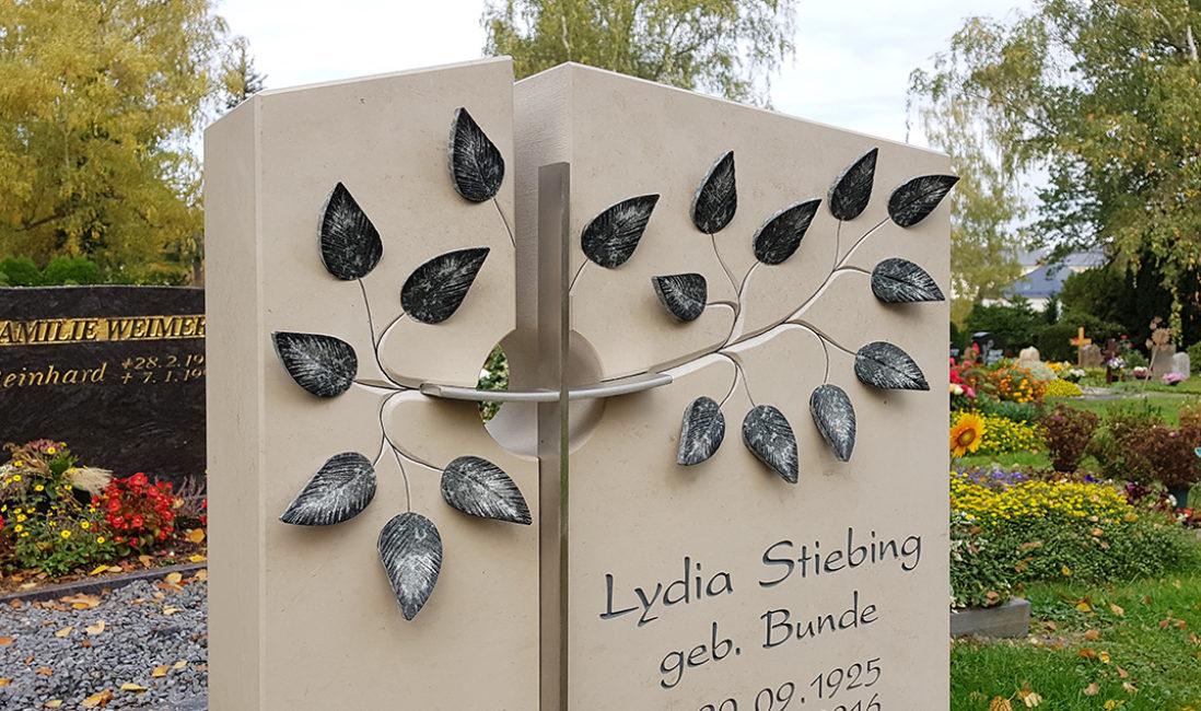 Grabstein Einzelgrab Kreuz Blätter Lebensbaum Kalkstein Metall Öffnung