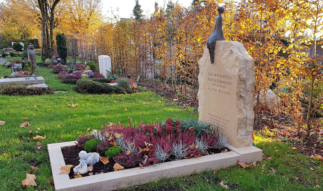 Einzelgrabstein Kalkstein Einfassung Bronzefigur sitzend Mensch Grabpflanzen Herbst Friedhofsgärtner München Vaterstetten