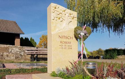 Impressionen vom Friedhof: Kalksteingrabmal mit Baum für ein Urnengrab