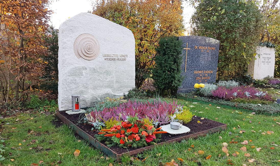 Doppelgrabanlage heller Grabstein Marmor Spirale gedreht Kalkstein Grabgestaltung Grabschmuck Blumengesteck Winter Herbstbepflanzung Beispiel