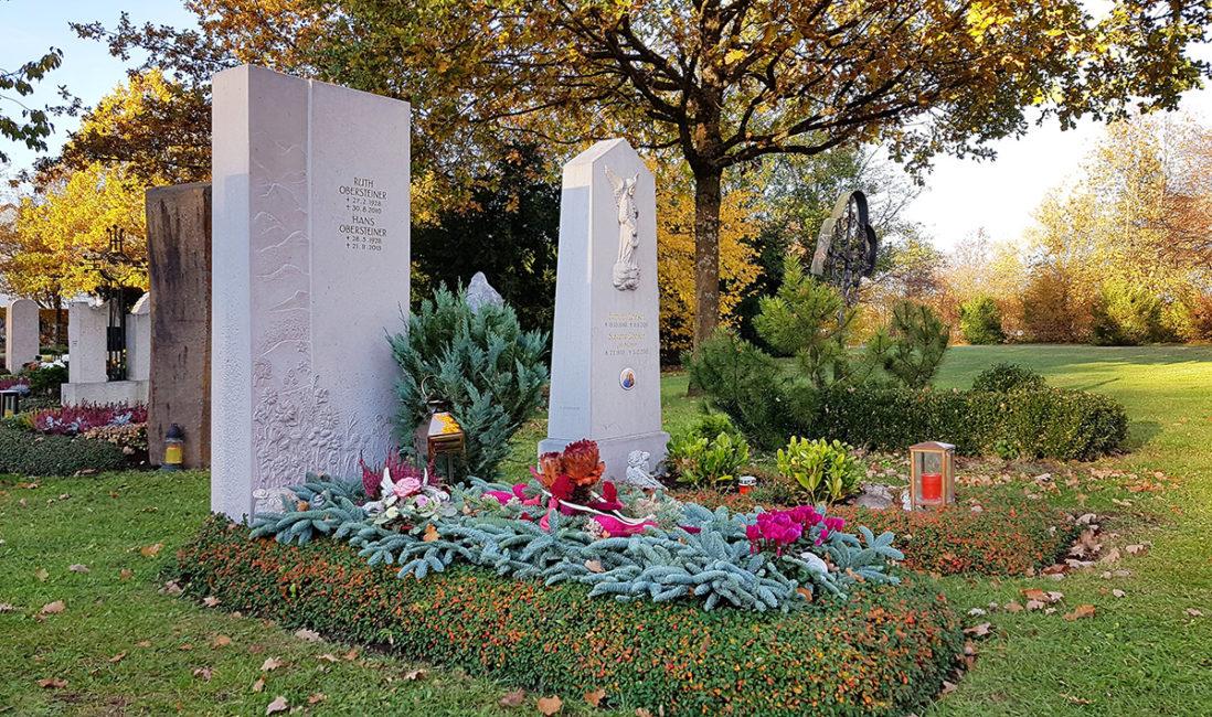 Einzelgrabstein Grabmal Kalkstein Ornament Wiese Grabpflanzen immergrün Winterbepflanzung Blumenschmuck Grabgesteck Friedhof Vaterstetten