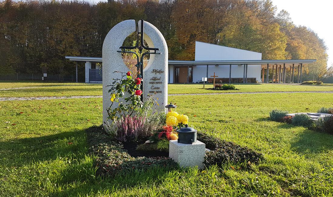 Grabmal Urnengrabstätte heller Granit zweiteilig Eisenkreuz schwarz Grabbepflanzung Rosen Symbol Grabschmuck Steinmetz Finsing München