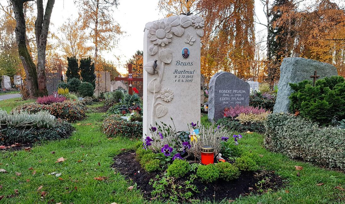 Urnengrab Grabstein Kalkstein Motiv Sonnenblume Vögel Bronzefigur florale Grabgestaltung Grabbepflanzung Herbst Steinmetz Vaterstetten München