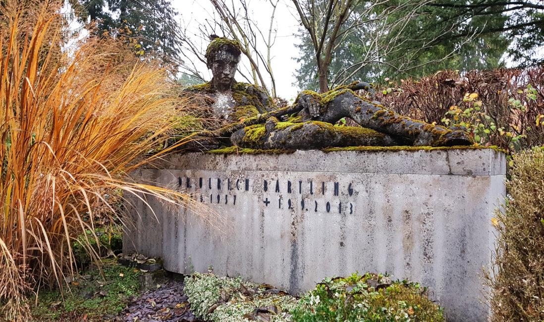 moderne Grabstelle Kalksteinblock mit Steinfigur liegend lebensgroß Mann Grabpflanzen immergrün Gräser Bodendecker Steinmetz Nordfriedhof Wiesbaden