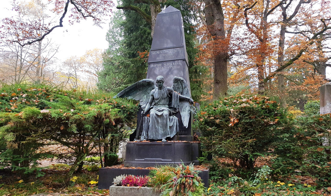 Familiengrabstätte Obelisk Stele schwarzer Granit Grabengel lebensgroß sitzend Flügel ausgebreitet Bronze Podest historisch Stufe Grabgestaltung Blumen Wiesbaden Nordfriedhof