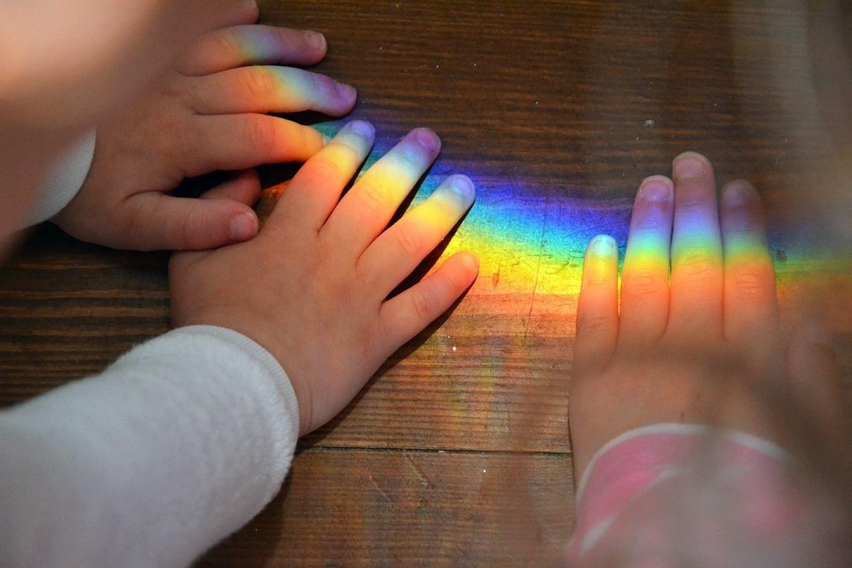 Kinderhand mit Regenbogen