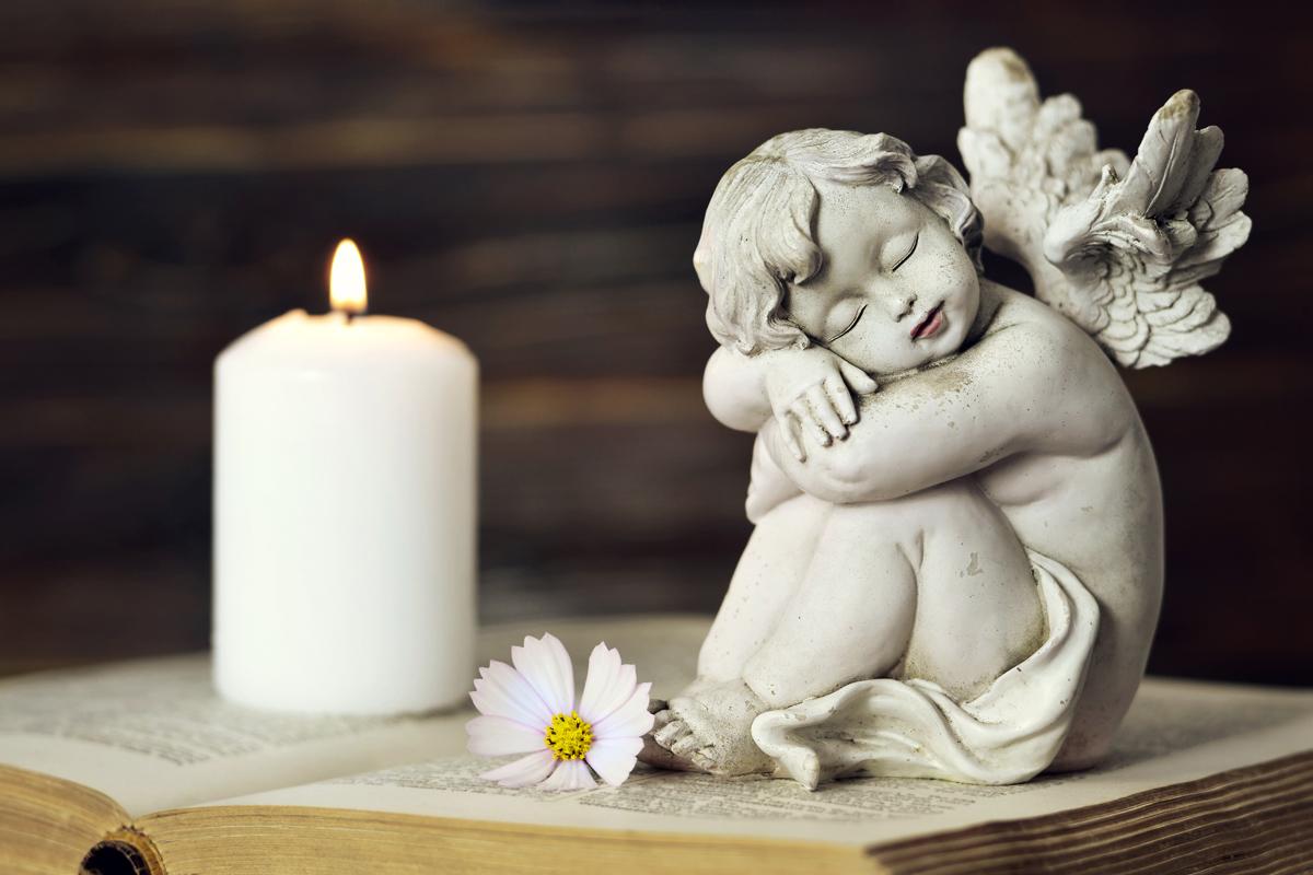 Kondolenzschreiben - Kleine Engelfigur auf einem Buch neben einer Kerze