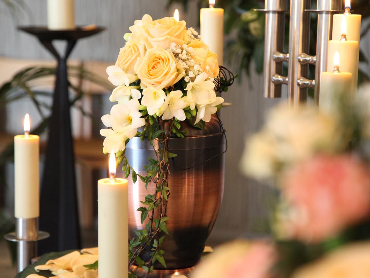 Trauerfeier mit einem großen Trauerstrauß auf der Urne & Kerzen
