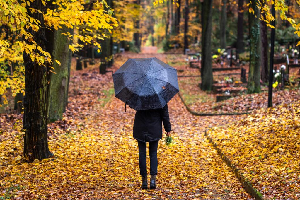 Frau im Friedhof bei Regen - Kondolenzbekundung